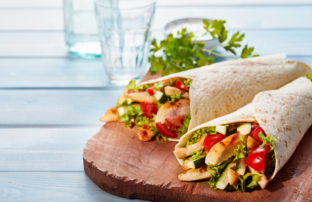 Photo for Two fresh chicken and salad tortilla wraps on wooden cutting board with glasses in background - Royalty Free Image