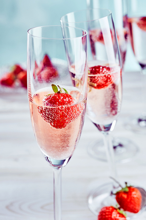 Foto de Pink champagne with fresh ripe strawberries served in a tall elegant flute for a special romantic occasion or aperitif - Imagen libre de derechos