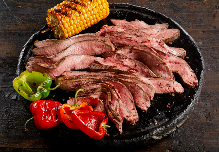 Photo for Grilled tender medium rare flank steak thinly sliced and served with roast corn on the cob and sweet peppers on a plate - Royalty Free Image