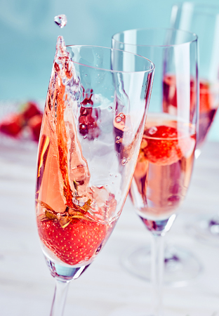 Photo for Champagne and strawberry splash with fresh fruit in a tilted flute of pink champagne with freeze motion on the drink in a close up view - Royalty Free Image
