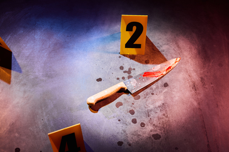 Photo for Bloody knife and blood stains marked with evidence number markers at crime scene - Royalty Free Image