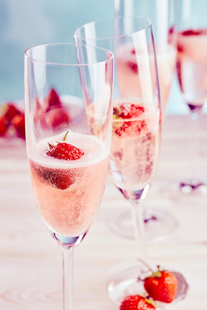 Photo for Delicious sparkling pink champagne with fresh strawberries served in stylish flutes for a romantic celebration or special occasion - Royalty Free Image