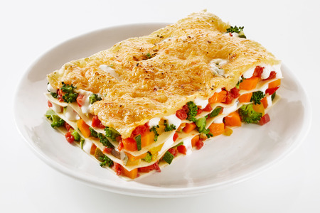 Foto de Healthy portion of fresh vegetable lasagne made with a mix of colorful fresh veggies served on a plate over a white background for menus and advertising - Imagen libre de derechos