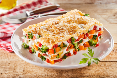 Photo for Large portion of healthy colorful vegetable lasagne made with assorted fresh veggies layered with melted mozzarella and pasta served on a white plate - Royalty Free Image