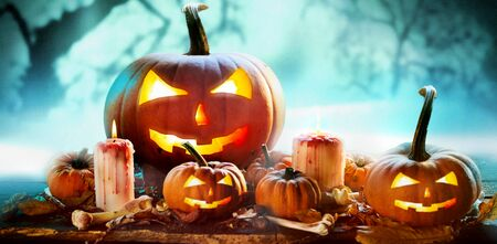 Photo for Spooky Halloween banner in a misty forest with an arrangement of glowing evil jack-o-lantern pumpkins and burning candles with dried leaves, bones and copy space - Royalty Free Image