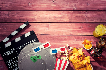 Photo for Various movie and film props including a clapperboard alongside popcorn, 3d glasses, tickets and refreshments in a cinematography themed image with timber wood grain copy space. - Royalty Free Image