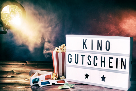Photo for Cinema movie theme with popcorn, 3d glasses and tickets illuminated by a spotlight shining through a smoky background with kino gutschein written on a word board. - Royalty Free Image