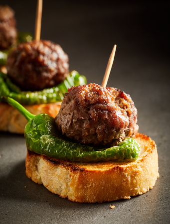 Photo pour Roasted meatballs with green pepper served on slice of baked bread - image libre de droit
