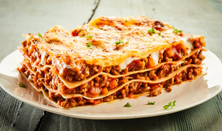 Foto de Slice of delicious beef lasagne on a plate garnished with chopped fresh parsley and viewed close up on the side showing the layers - Imagen libre de derechos