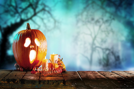 Foto de Spooky halloween theme of jack o lantern with candles standing on wooden table against trees - Imagen libre de derechos