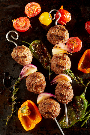 Foto de Roasted meatballs with peppers, garlic, tomatoes against dark background - Imagen libre de derechos