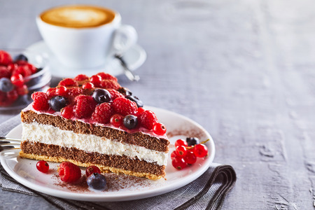 Photo pour Piece of layered creamy fruit cake with raspberries and blackberries against cup of coffee - image libre de droit