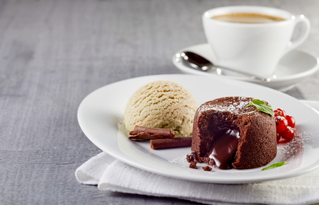 Photo for Chocolate lava cake with ice cream served on plate against cup of coffee - Royalty Free Image