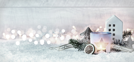 Photo for Wintry Merry Christmas festive panorama banner with a decorative arrangement of pine cones and branches with a burning candle and cottage in fresh white snow against a sparkling bokeh of party lights - Royalty Free Image