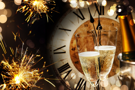 Photo pour Festive New Years background with sparklers and champagne in front of a clock counting down to midnight with sparkling bokeh on darkness - image libre de droit