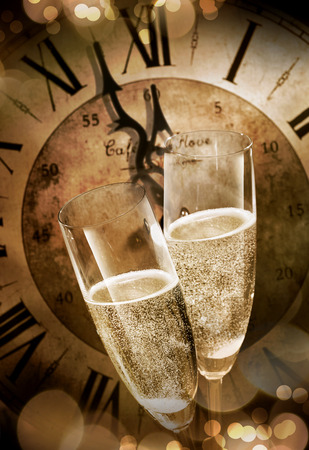 Foto de Close-up of two champagne flutes toasting before midnight against a vintage clock during romantic celebration at New Years Eve - Imagen libre de derechos
