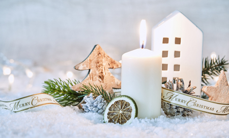 Photo for Merry Christmas winter still life with fresh white snow, pine cones and foliage and a burning candle in front of a cottage - Royalty Free Image