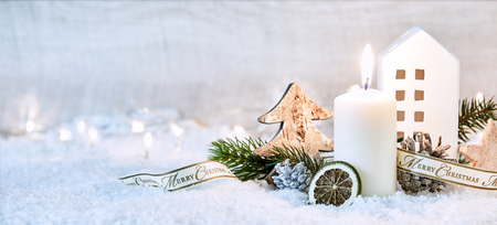 Photo for Festive white winter Christmas panoramic banner with a glowing candle amongst decorative ornaments in snow with a sparkling bokeh of party lights and copy space behind - Royalty Free Image
