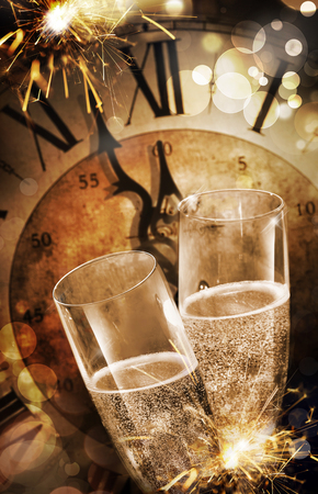Photo for Close-up of two champagne flutes toasting against a vintage clock before midnight during party with fireworks for celebrating New Year - Royalty Free Image