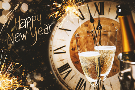 Foto de Happy New Year greeting card with champagne in front of a clock counting down to midnight and a sparkling bokeh of party lights and sparklers - Imagen libre de derechos