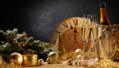 Foto de Wide angle New Years banner with flutes and a bottle of champagne in front of a clock counting down to midnight and copy space above assorted gold seasonal holiday decorations - Imagen libre de derechos