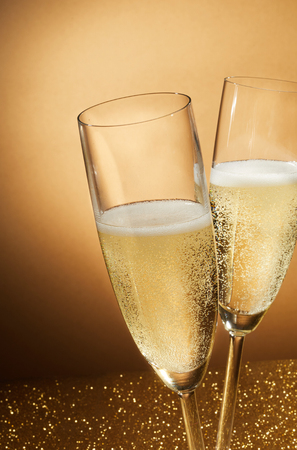Photo for Two romantic flutes of sparkling champagne on a glitter background conceptual of a party celebration for an anniversary, wedding, New Year or Valentines Day - Royalty Free Image