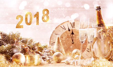 Photo for 2018 festive gold background with two flutes of sparkling champagne in front of a clock counting down to midnight and assorted festive holiday decorations - Royalty Free Image