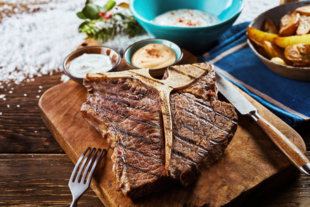 Photo for Piece of grilled t-bone steak on wooden cutting board in close up view - Royalty Free Image