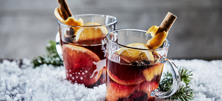 Foto de Panorama banner with two glasses of Christmas Gluhwein or mulled red wine garnished with stick cinnamon and served on winter snow with copy space - Imagen libre de derechos