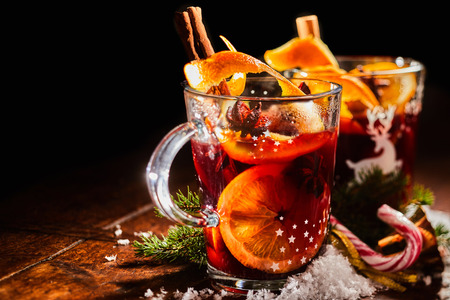Photo pour Traditional Christmas Gluhwein or mulled sweet spicy red wine with cinnamon served in two glass mugs with candy canes and copy space - image libre de droit
