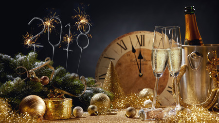 Photo pour 2018 festive golden New Year still life with sparkler date, clock ready to strike midnight, decorations and two flutes of sparkling champagne - image libre de droit