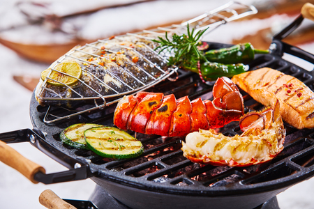 Foto de Winter barbecue with gourmet seafood grilling over the hot coals including a lobster tail, salmon and whole marine fish seasoned with herbs - Imagen libre de derechos