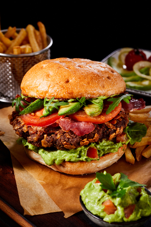 Photo for Wholesome gourmet burger with avocado, crispy bacon and guacamole on a juicy meat patty served on brown paper with side dishes - Royalty Free Image
