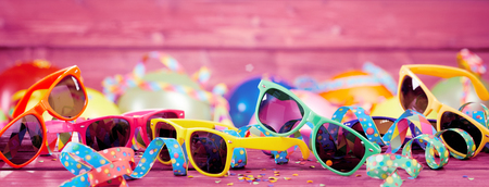 Photo pour Party banner with colorful confetti, streamers and plastic sunglasses on pink wooden board with copy space - image libre de droit