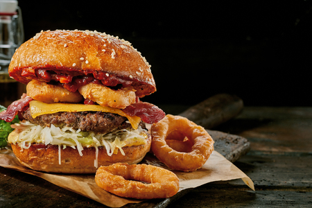Photo pour Gourmet Surf and Turf burger with squid rings, crisp bacon, beef patty and cheese served on a rustic wooden board over a dark background with copy space - image libre de droit