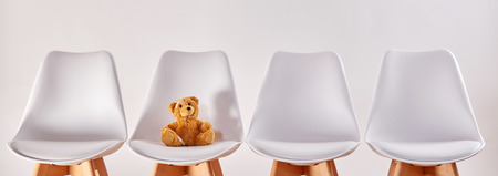 Foto de Cute brown teddy bear on a seat in the waiting room with empty chairs of a hospital or a health center for children - Imagen libre de derechos