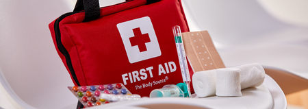 Foto de Small red First Aid kit with pills, bandages and a thermometer on the seat of a chair in a concept of triage and healthcare - Imagen libre de derechos
