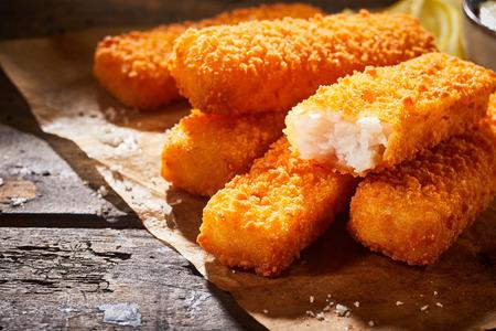 Foto de Close-up of delicious deep fried fish fingers served on paper on a rustic wooden table - Imagen libre de derechos