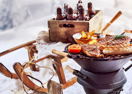 Foto de Winter barbecue outdoors in the snow with T-bone steaks and sausages sizzling on the grill and a crate of beers on a wooden sled - Imagen libre de derechos