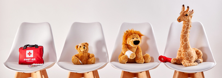 Foto de Three cute stuffed animal toys on chairs in the waiting room of a modern hospital or health center for children - Imagen libre de derechos