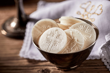 Foto de Bowl of sacramental bread or Hosties ready for the Holy Communion service representing the body of the resurrected Christ showing detail of the cross - Imagen libre de derechos
