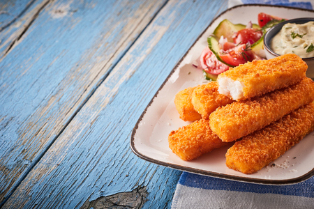 Photo for Tasty oven baked fish fingers with salad and tartare sauce served on a platter on a rustic weathered blue wooden table with copy space - Royalty Free Image