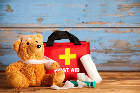 Photo pour Paediatric healthcare concept with a little teddy bear with its arm in a sling alongside a first aid kit and bandages on rustic wood - image libre de droit