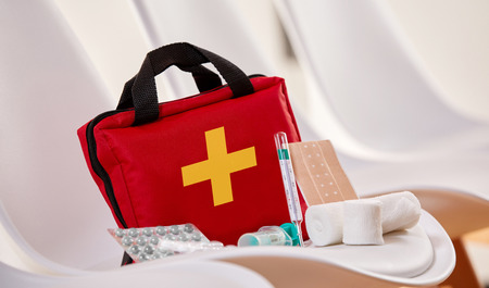Foto de Close-up of a first aid kit with sterile bandages, pills and syringe for emergency in the waiting room of a hospital or health center - Imagen libre de derechos