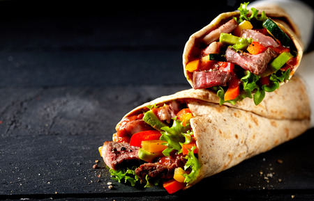 Photo pour Tortilla wraps with tender sliced roasted entrecote beef steak, red chili pepper and salad trimmings on a dark slate background with copy space - image libre de droit