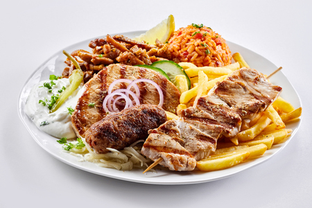 Photo for Mixed grill Greek platter with souvlaki, souzuki steak and spicy pork skewers served with tomato rice pilaf, potato chips and salad - Royalty Free Image