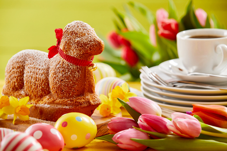 Photo pour Delicious novelty lamb shaped Easter cake with a red ribbon collar on a spring table set with tulips, Easter eggs, plates and coffee - image libre de droit