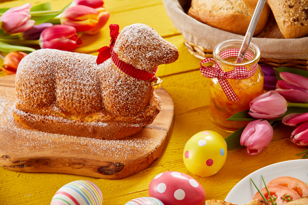 Foto de Gourmet lamb shaped Easter cake with colorful eggs and tulips on a festive table - Imagen libre de derechos