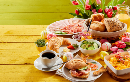 Photo pour Easter buffet breakfast or brunch with assorted bread rolls, cheese, meat, scrambled egg, orange juice, coffee on a wooden table decorated with easter eggs and spring flowers with copy space - image libre de droit