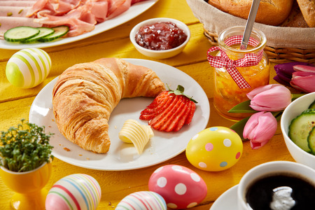 Photo for Delicious Easter breakfast on a decorated table with colorful eggs and a freshly baked croissant and strawberry served with jam, cold meats, cheese and coffee - Royalty Free Image